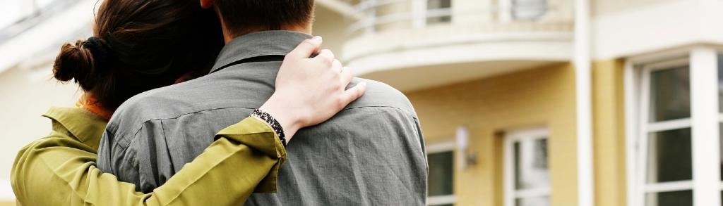 Ein Paar hält sich in den Armen und begutachtet eine Immobilie.
